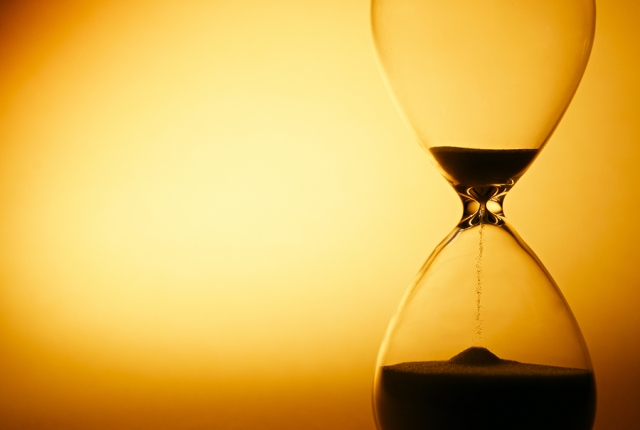 Sand passing through the glass bulbs of an hourglass measuring the passing time as it counts down to a deadline or closure on a yellow background with copyspace