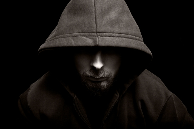 Portrait of scary evil man with hood in darkness